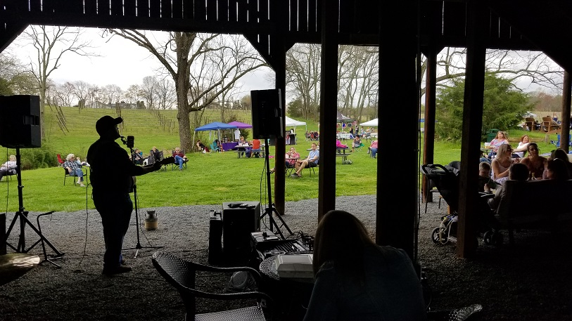 Single Musician under the barn playing music